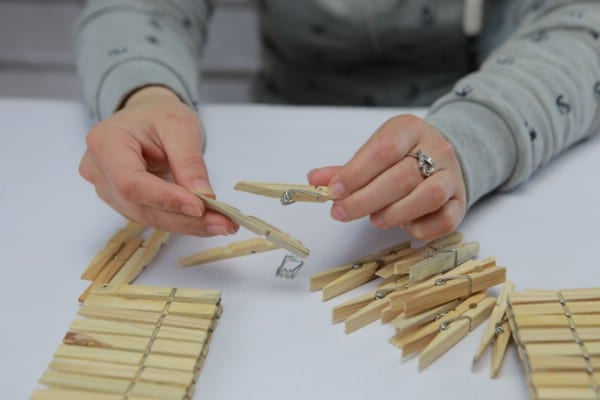 Taking apart wooden clothespins to remove springs