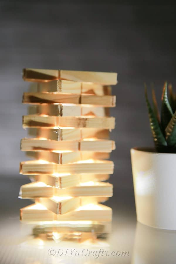 Side view of clothespins turned into a candle cover