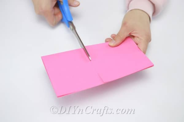 Cutting pink paper into small squares