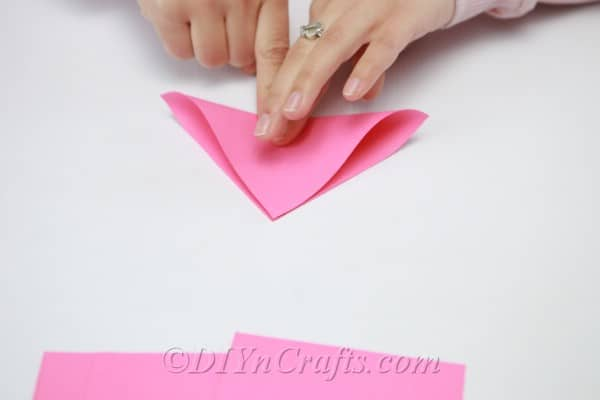 Folding pink paper into a small triangle