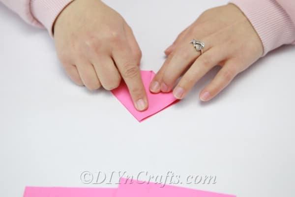 Folding pink triangle into a rectangle shape