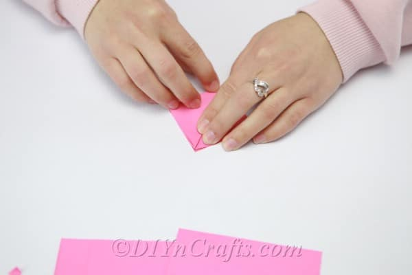 Folding pink paper into tiny triangle
