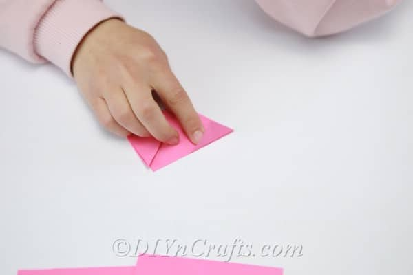 Continuing to fold pink paper into a flower