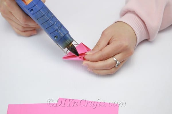 Gluing pink paper to hold its flower shape