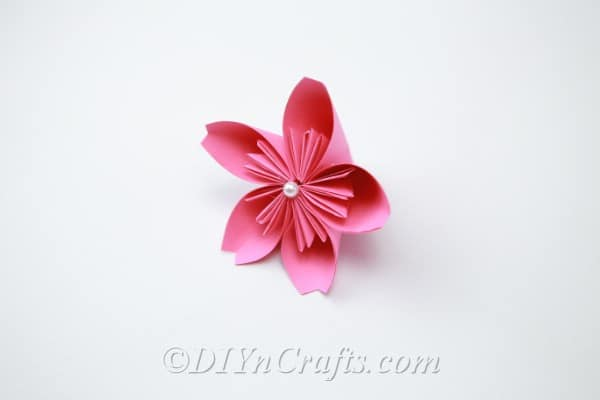 Pink paper flower with a pearl glued to the center