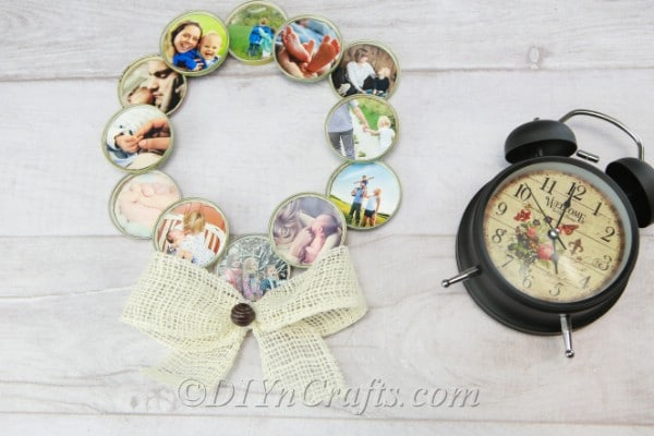 Photo wreath beside a black alarm clock