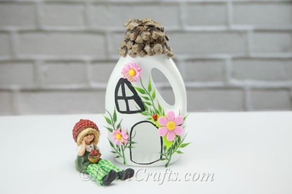 Fairy house with a fairy sitting next to it