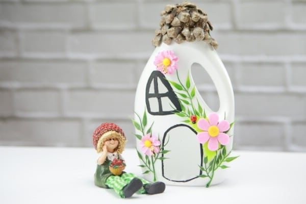 Fairy house jug beside a fairy figurine