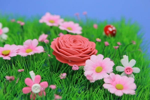 Foam flower on grass with pink flowers