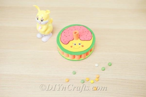 Foam donut box beside a bunny figurine