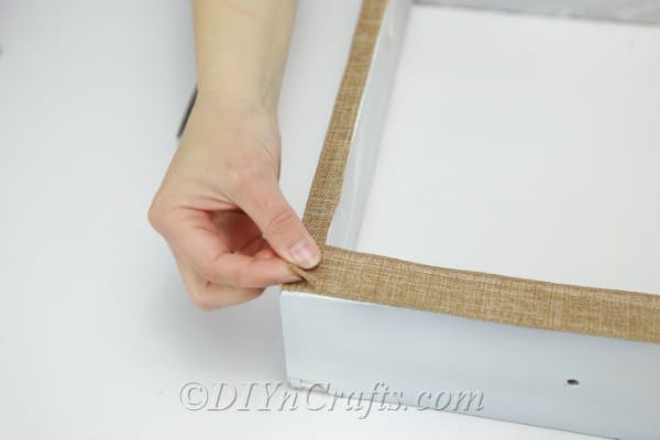 Gluing burlap onto the front of a wooden box