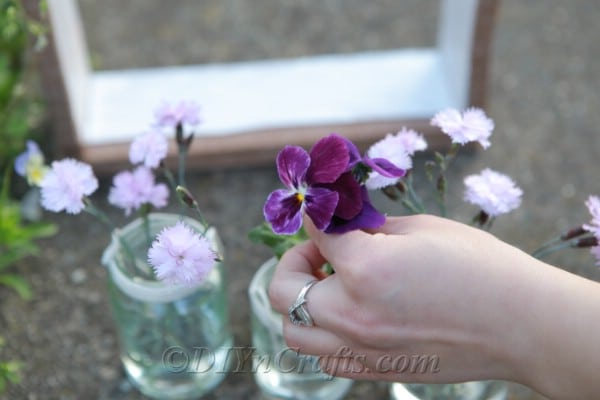 Adding flowers to glass jars