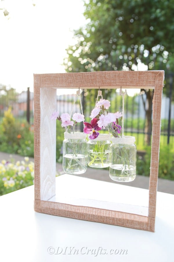 Up close image of wooden box with hanging vases and purple flowers