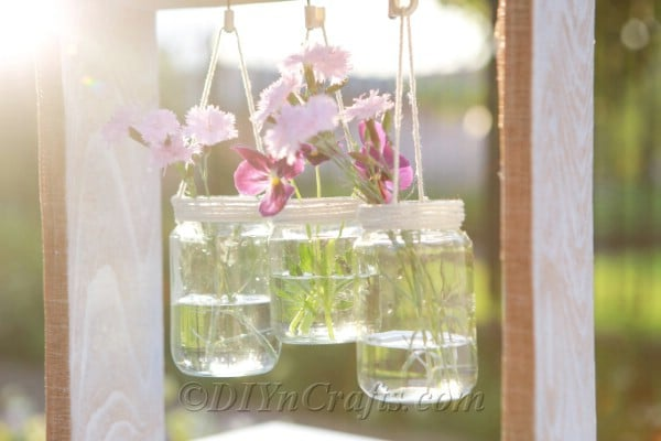 Wooden box slanted with hanging glass jars
