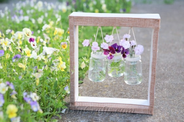 Hanging wooden box with jars of flowers