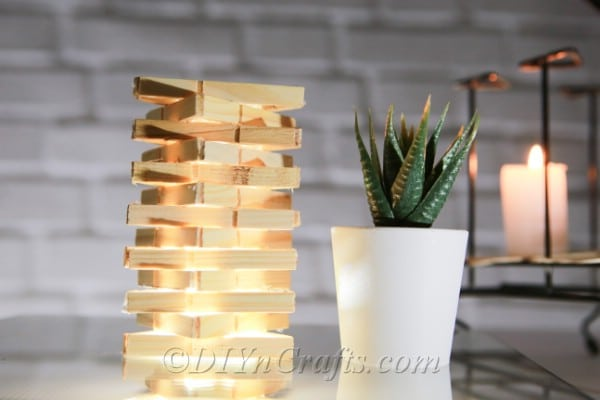 Clothespin lamp beside a small plant