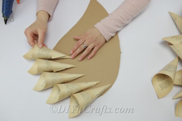 Covering cardboard wing with book page cones