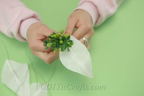 Adding greenery to a white tissue paper flower