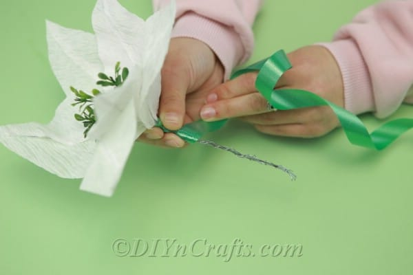 Covering floral wire with green ribbon
