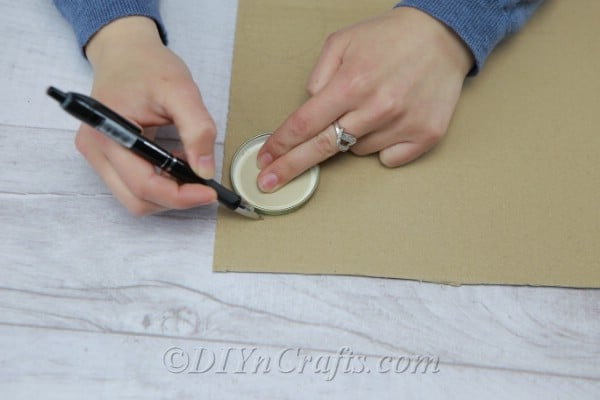 Tracing lids onto cardboard