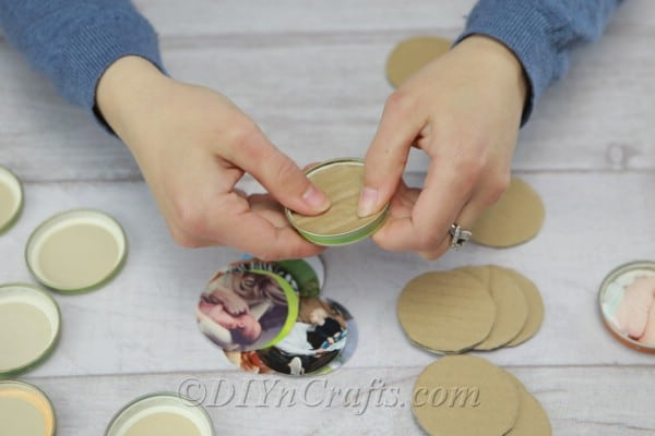 Placing cardboard circles into lids
