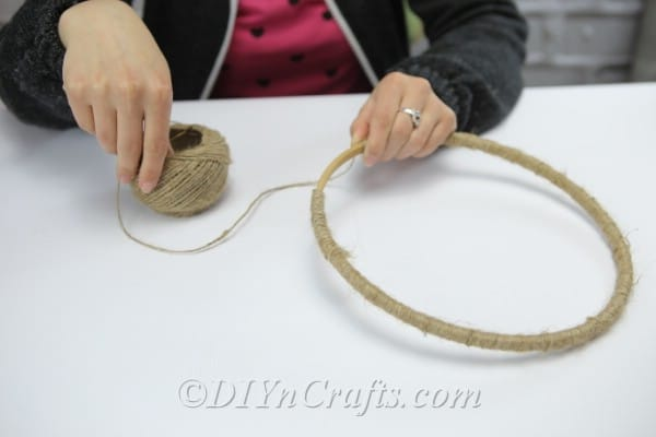 Continue winding the twine around the wooden hoop.