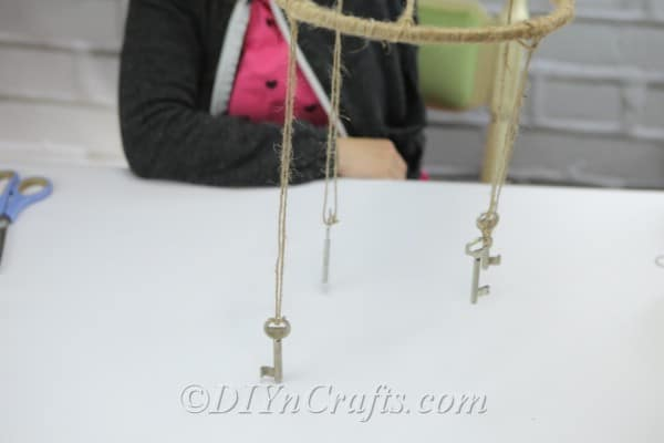 Hang keys from strands of twine from the hoop.