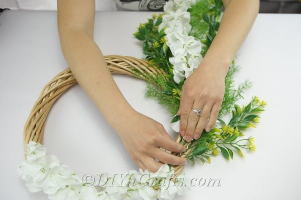Keep arranging and attaching the flowers to the wreath.