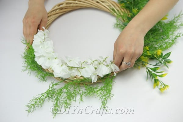 Attach some greenery to the top of the wreath.