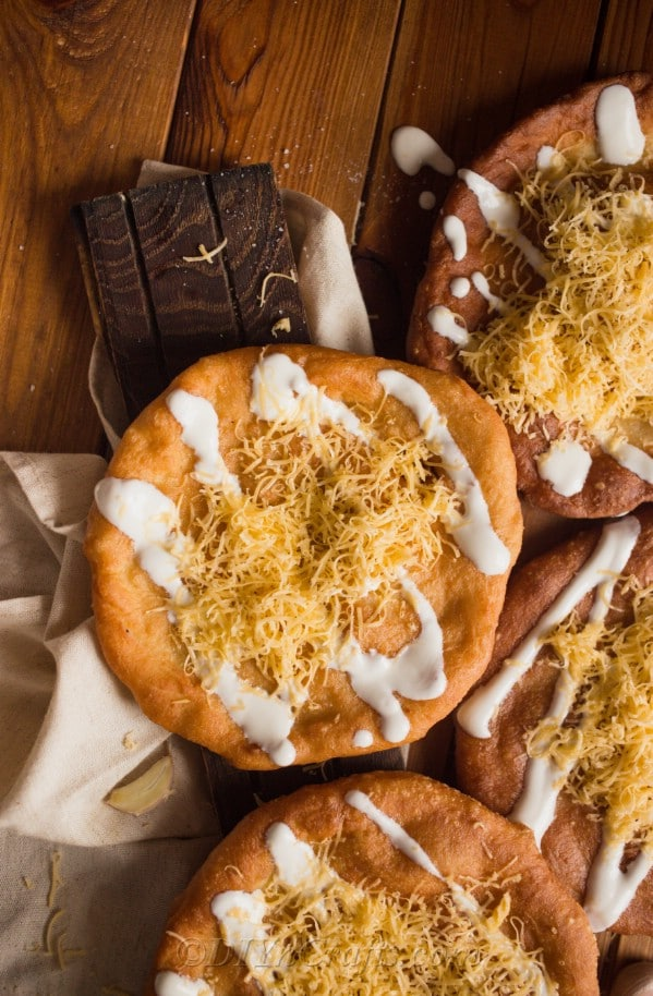 Hungarian langos topped with shredded cheese and sour cream