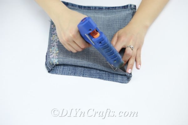 Fold up a bit of fabric at one end of the pant leg and apply glue so that you can close the pant leg.