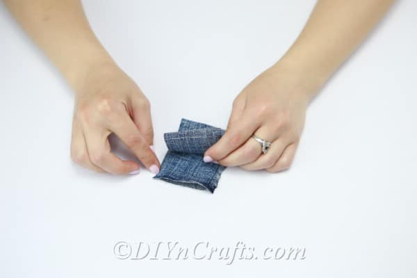 Fold the strip of denim in half repeatedly.