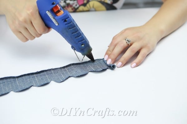 Put glue along the straight edge of the denim strip.