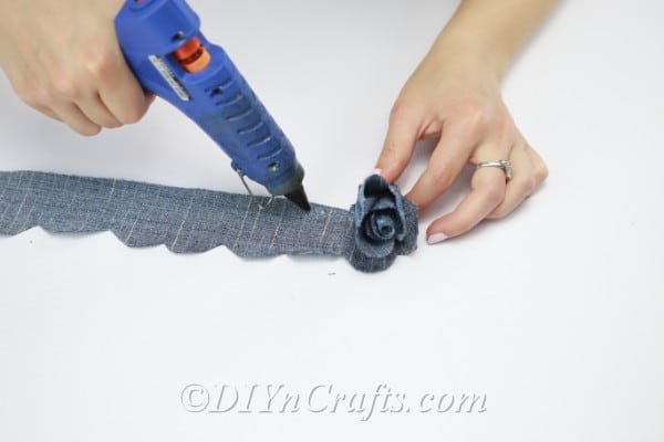Continue to roll up the strip of denim, applying the glue while you do.
