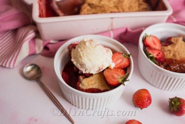 Dish of strawberry cobbler with vanilla ice cream