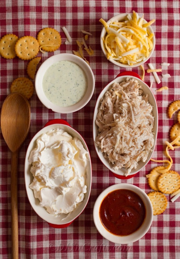 Ingredients for easy buffalo chicken dip in bowls and laying on a red and white checkered cloth
