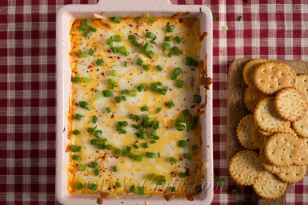 buffalo chicken dip prepared in a casserole dish topped with sliced green onions