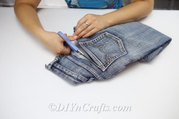 Woman cutting the pockets out of a pair of blue jeans for the denim bag