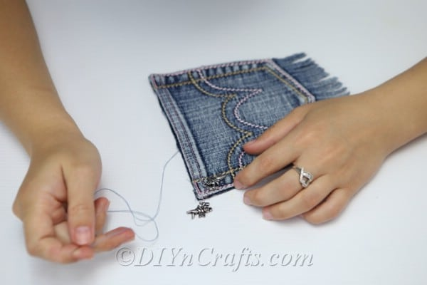 Sewing on an embellishment on the pocket of the denim bag
