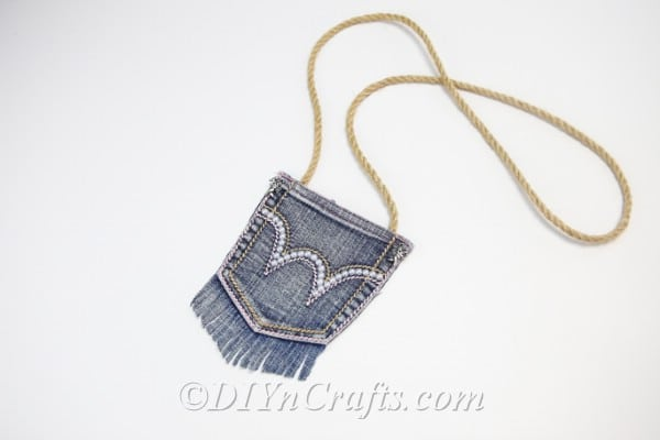 Finished denim bag with pearl embellishment laying on a white table