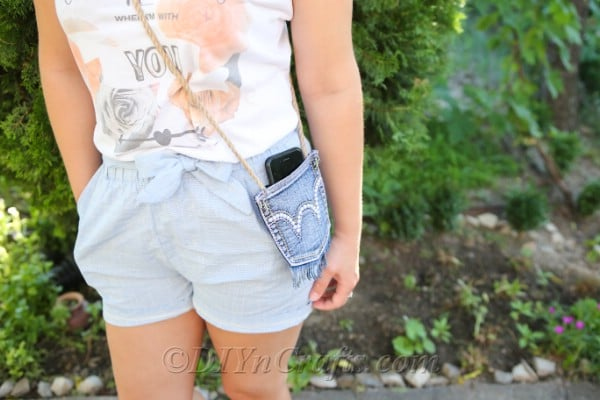 Denim bag showing pocket holding phone on a woman who is standing in a garden