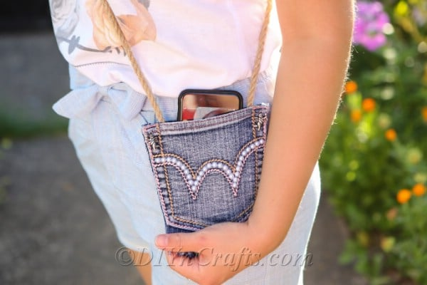 Woman carrying diy denim bag across shoulder and showing phone peaking out the top of pocket