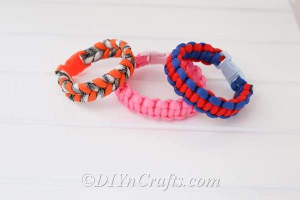Square knot bracelets stacked together on a white surface