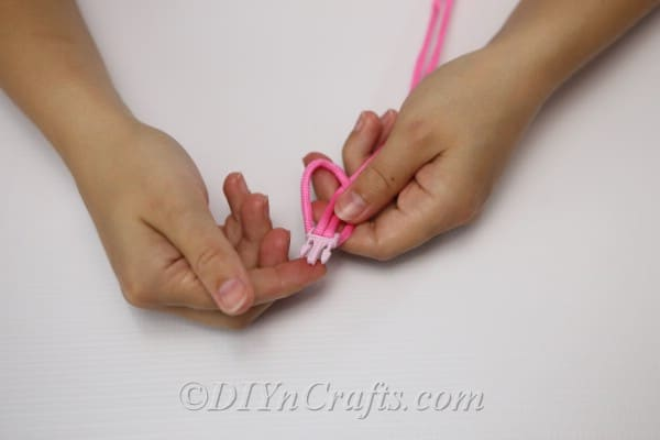 Threading cord through bracelet clip to secure before knotting