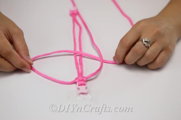 Close up picture of woman making the p shape for a square knot bracelet