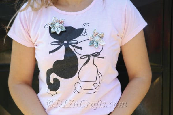 Two fabric flowers pinned to a worn t-shirt.