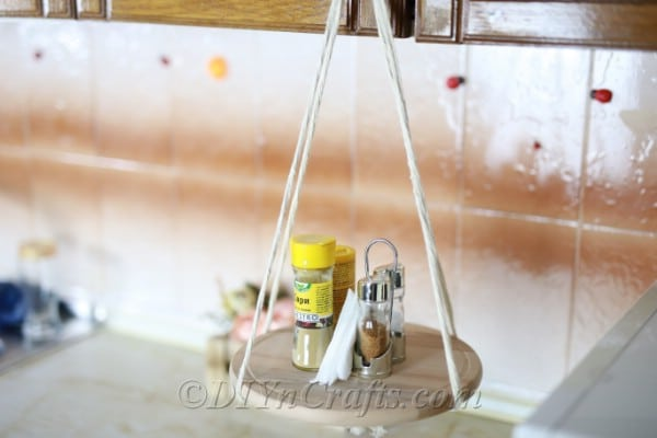 A hanging shelf with supplies in a kitchen.