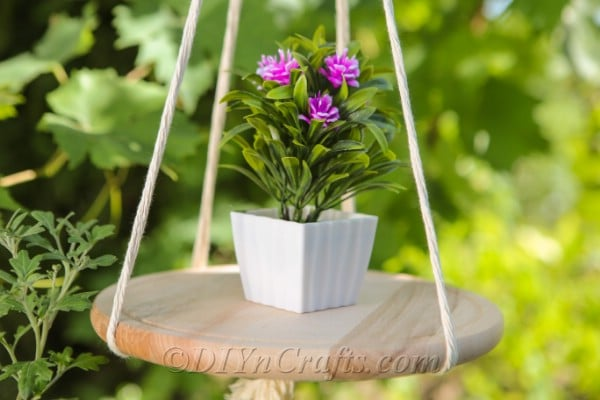 A close-up of a hanging shelf with a potted plant on it.