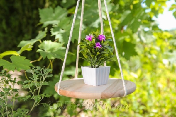 A DIY hanging shelf with a flower on it and foliage in the background.