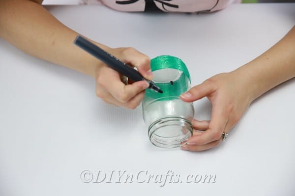 Draw watermelon seeds onto the outside of the jar with the black marker.